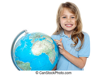 Young girl selecting holiday destination over globe -...