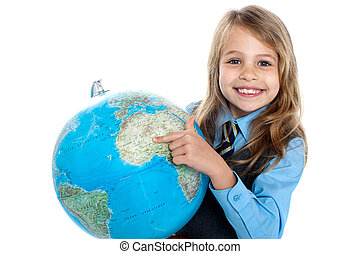 Pretty school child holding globe and pointing - Where are...