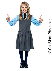 Pretty school child showing thumbs up gesture - Charming...