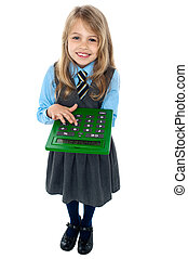 Pretty child in school uniform using calculator