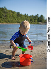 Toddler at Beach - toddler playing with shovel and bucket at...