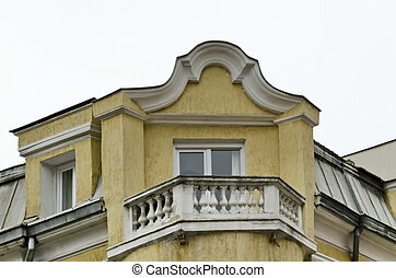 Old building - last floor with balcony a stone fence and...