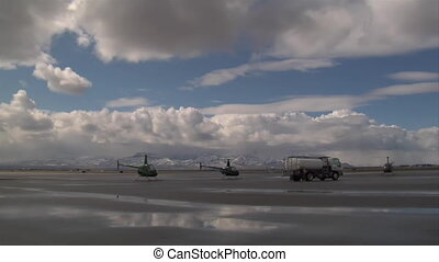 time lapse of helicopters on runway and puffy clouds
