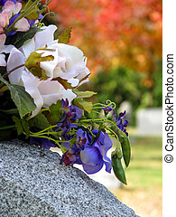 grave flowers - silk flowers on a cemetery grave headstone