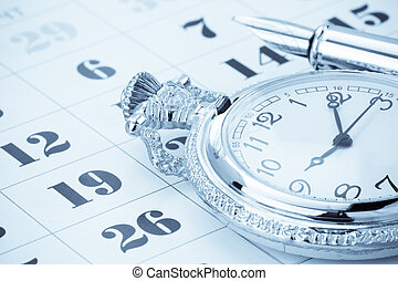 ink pen and watch on calendar