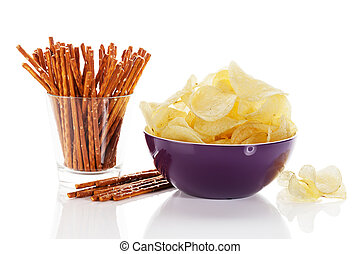 potato chips in a bowl with pretzel sticks in a glass on...