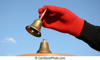 two brass bells and hand with red glove