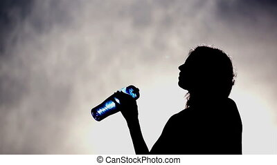 Silhouette of Woman Drinking Water - Silhouette of a woman...