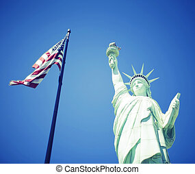 Statue of Liberty next to the American flag