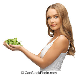 woman with spinach leaves on palms - bright picture of woman...