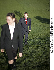 Business Team - Two businesspeople climbing hill together...