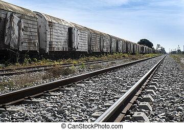 old rusty train wagons on railway under sungliht