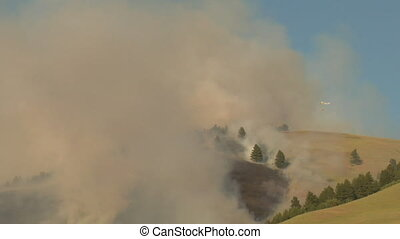forest fire burns with helicopter