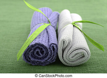 Purple and green wash cloths rolled up for bath at spa