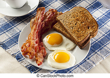 Organic Sunnyside up Egg with toast and bacon for breakfast