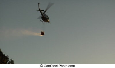 firefighting helicopter flies into sunset