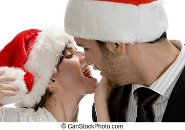 couple kissing and wearing santa cap against white...