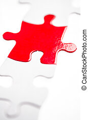 Red jigsaw piece - Red jigsaw puzzle piece in a line of...