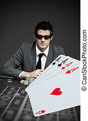 Gambler in sunglasses with digital cards in foreground