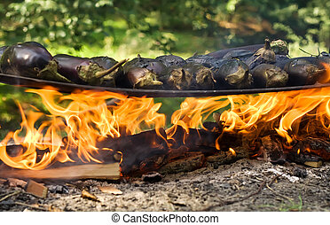 Eggplants cooking on a metal plate over open fire