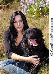 My dog - Caucasian girl and a black dog in the field