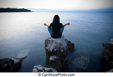 Meditation by the sea at dusk - Girl meditating by the sea...