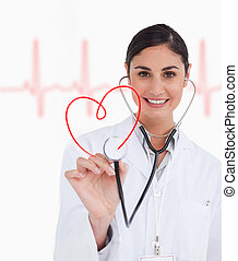 Happy doctor holding up stethoscope to red heart design on...
