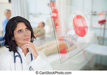 Doctor looking up at screen showing red ECG data in hospital...
