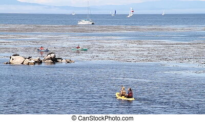 Kayakers paddle, boats in background