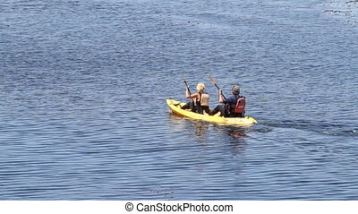 Two fit kayakers paddle across water