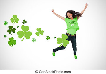 Girl wearing St Patricks day t-shirt jumping for joy on...