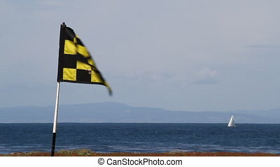 golf flag blowing wind with ocean and sailboat in distance