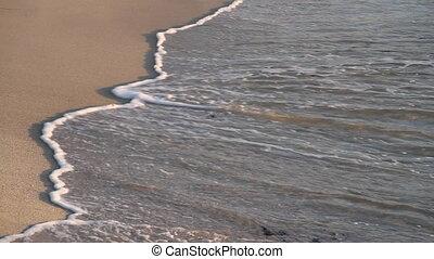 waves break on sandy beach