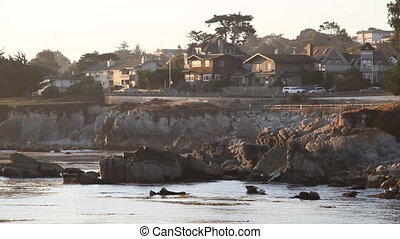 houses above rocky shoreline at sunrise
