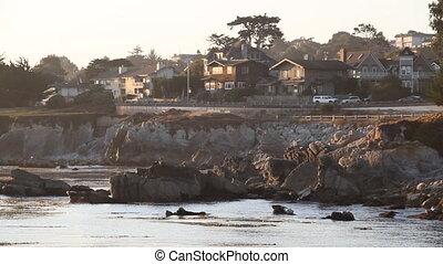 houses above rocky shoreline at sunrise