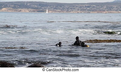 scuba divers enter water