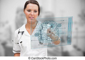 Concentrated nurse working on a medical interface in the...