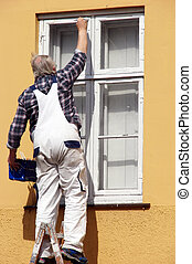 Painting - old man is painting the window