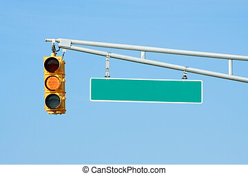 Yellow traffic signal light with sign on blue sky