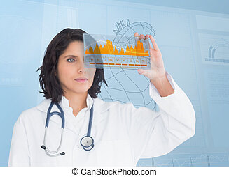 Brunette doctor looking at a graph with futuristic...