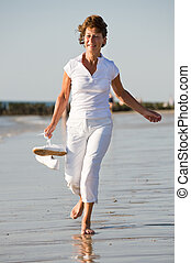 Active senior at the beach - Active and happy senior woman...