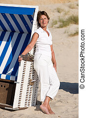 At the beach - Active senior woman with white clothes is...