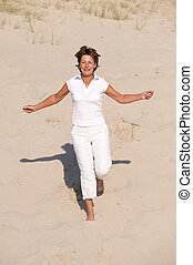 Jumping at the beach - Active senior woman with white...