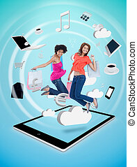 Two cute women jumping on a tablet pc against a digital blue...