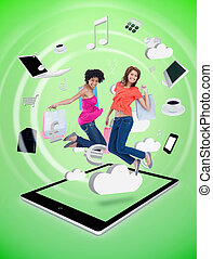 Two happy women jumping on a tablet pc against a digital...