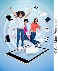 Three cute women jumping on a tablet pc against a digital...