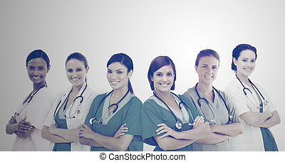 Female hospital workers standing arms folded in line in a...