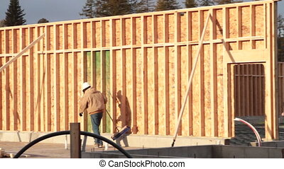 construction worker walks along newly built wall