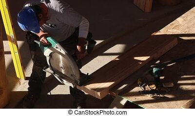 worker cuts wood with saw
