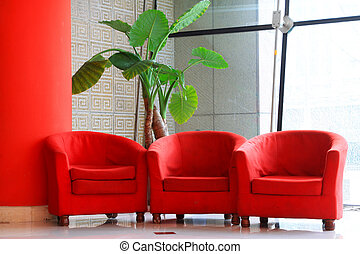 red sofa and green flowers in the hall in a public place